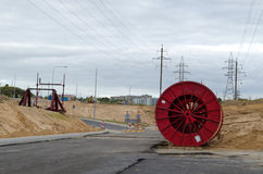 High voltage cable reels road construction. Huge high voltage cable reels in power line construction site. road building work and electricity line laying Royalty Free Stock Images