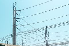 High voltage cables for electricity transmission over roof on blue sky background stock photo