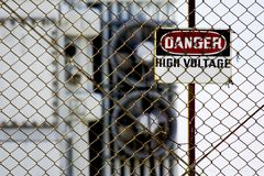High Voltage Danger Sign. Danger High Voltage sign on chainlink fence surrounding power station Royalty Free Stock Image