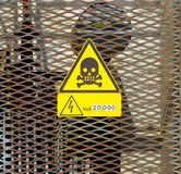 High voltage danger sign with the skull icon, symbol of death, and the information about the electric power present in the plant. Royalty Free Stock Photography