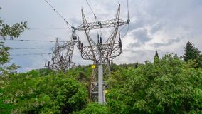 High voltage elecricity pylons come outside a green forest stock photography