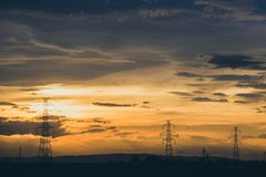 High voltage electic pylon line on party cloud sunset stock photography