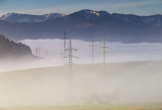High voltage electric lines in fog Royalty Free Stock Photo