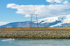 High voltage electric poles located in countryside, Iceland. High voltage electric poles and beautiful snow mountain landscape located in countryside, Iceland stock photo