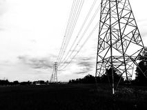 High voltage electric power pole with various wiring through rice field. stock photography