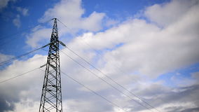 High voltage electric power pylon and lines with time lapse clouds in background. Stock Images