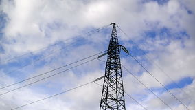 High voltage electric power pylon and lines with time lapse clouds in background. Stock Photo