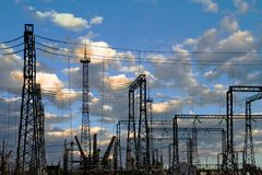 High voltage electric power station - electric poles and lines on blue sky with clouds background. Creative still royalty free stock photos