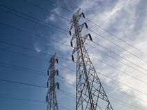 High voltage electric tower with blue sky color pop background. In horizontal Stock Photography