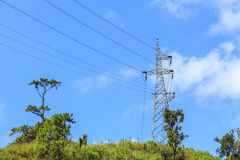High voltage electric tower on the mountain and blue sky. Background Stock Photo