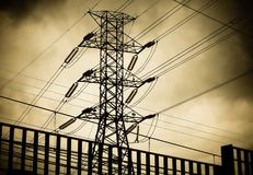 High voltage electric tower or pylon and power lines silhouette against dark cloudy sky. Royalty Free Stock Photo