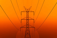 High Voltage Electric Transmission Tower Energy. Pylon against the sunset background Stock Photo