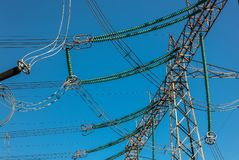 High voltage electrical power lines and isolators against a blue. Sky Royalty Free Stock Image