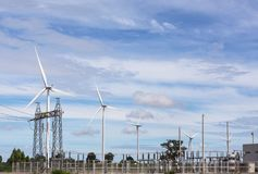 High voltage electrical power pylon substation  with wind turbines renewable wind energy Stock Photos