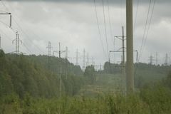 High voltage electrical transmission towers electricity pylons and power lines on green field Royalty Free Stock Photo