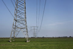 High voltage electrical transmission towers electricity pylons a Royalty Free Stock Image