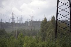 High voltage electrical transmission towers electricity pylons and power lines on green field Stock Image