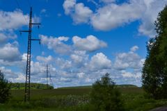 High voltage electrical transmission towers and power lines on field Stock Photo