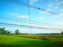 The high-voltage electricity pole leaning over the green fields. And the clouds are floating in the blue sky Stock Photography