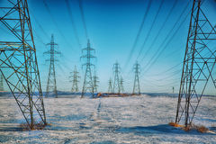 High-voltage electricity power pylons. Group of high-voltage electricity power pylons over blue sky and snow covered countryside, Canada Stock Image