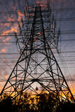 High voltage. Electricity pylon against the evening sky look like a flame for background Stock Photography