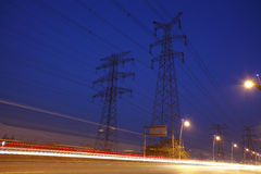 The high voltage electricity pylon in side of highway Royalty Free Stock Photography