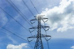 High voltage electricity pylon and transmission line with beautiful blue sky and cloud background in sunny day Royalty Free Stock Images