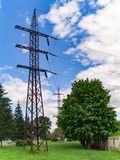 Image of high voltage power line and sky. High voltage electricity pylon and transmission power line on the blue sky and white clouds on the background Stock Image