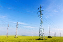 High voltage electricity pylons. In a field against blue sky Stock Photography