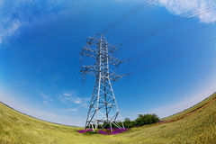 High-voltage electricity pylons against blue sky Royalty Free Stock Image