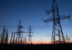 High voltage electricity pylons against sunset. Electric pole power lines and wires Royalty Free Stock Photo