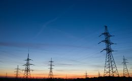 High voltage electricity pylons at beautiful sunset. Electric pole power lines and wires. High voltage electricity pylons at beautiful sunset Stock Image