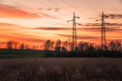 High voltage electricity pylons in a field and orange sky at sunset Stock Photo