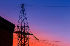 High voltage electricity pylons and transmission power lines on the blue sky background. Stock Photography