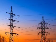 High voltage electricity pylons and transmission power lines on the blue sky background. Royalty Free Stock Images