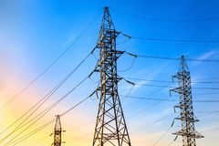 High voltage electricity pylons and transmission power lines on the blue sky background. stock photos