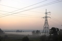 High voltage electricity transfer lines and pylon in a fog. Gy morning stock image