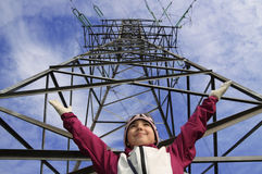 High-voltage electricity transmission line. Child holds up his hands near electricity transmission line Royalty Free Stock Image