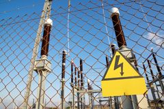 High voltage hazard. Electrical hazard sign placed on a metal fence royalty free stock photos