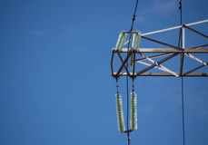 High-voltage insulator of electricity transmission line. Against clear blue sky Royalty Free Stock Photos