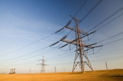 High voltage land. Field with high voltage electricity pylons Royalty Free Stock Images