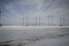 High-voltage line on the background of a winter landscape - blue sky and snow-covered field royalty free stock photography