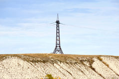 High voltage line and electricity pylon on coastline of river. Royalty Free Stock Images