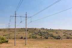 The high-voltage line in the steppe . The high-voltage line in the steppe among fields and heights in a dry grass and trees against the background of Stock Photo
