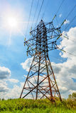 High voltage line and sun in cloudy sky Royalty Free Stock Image