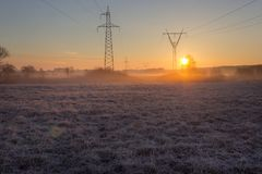 High voltage line supports in fog at frosty spring sunrise morning stock image