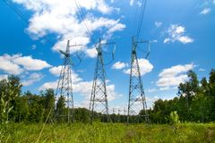 High voltage lines in a forest clearing royalty free stock photo