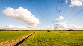 High voltage lines and power pylons in a Dutch agricultural land. Scape with large meadows. Diagonal in the image is a long ditch. It is a sunny day with a royalty free stock image