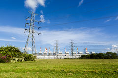 High voltage lines and power pylons in a flat and green agricultural landscape Stock Images