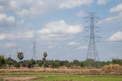 High voltage lines and power pylons in a flat and green agricultural landscape royalty free stock image